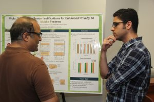 Professor Sharad Mehrotra talking with a student at the Computer Science Research Showcase